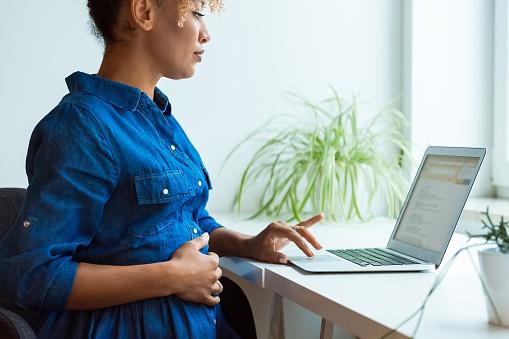 Pregnant Entrepreneur Using Laptop At Desk Stock Photo - Download Image Now