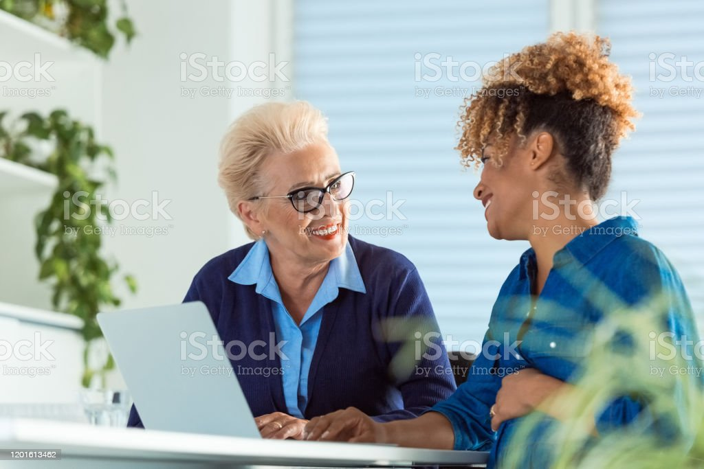 Pregnant executive looking at elderly role model Smiling female executives talking while using laptop. Pregnant businesswoman looking at elderly role model in meeting. They are discussing at desk in office. 35-39 Years Stock Photo