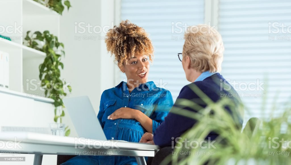 Pregnant executive talking with senior colleague Pregnant executive talking with senior colleague. Owners are working at desk in office. They are running start-up business. 35-39 Years Stock Photo
