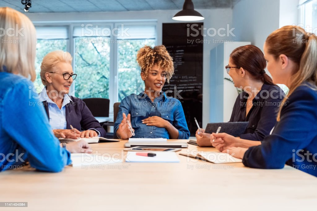 Pregnant expertise talking with colleagues at desk Pregnant expertise talking with colleagues while sitting at desk. Female professionals are running new business. They are working in team at office. 35-39 Years Stock Photo
