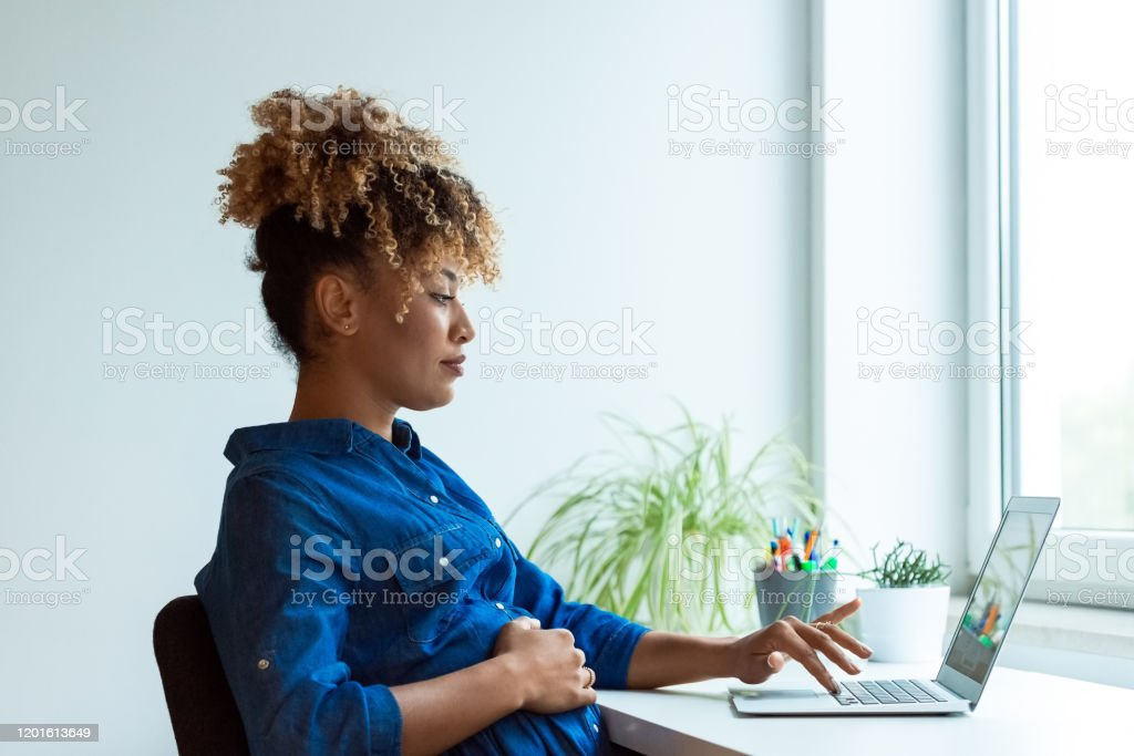 Pregnant expertise working on new business plans Side view of pregnant expertise working on new business projects at desk. Female professional is using laptop in office. She is wearing business casuals. 35-39 Years Stock Photo