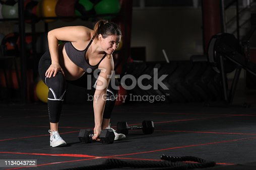 Pregnant female athlete doing single sumo deadlift high pull with dumbbell