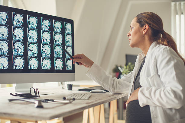 Pregnant female doctor examining brain scan Pregnant female doctor sitting at desk in doctor's office examining brain scan. neurosurgery stock pictures, royalty-free photos & images