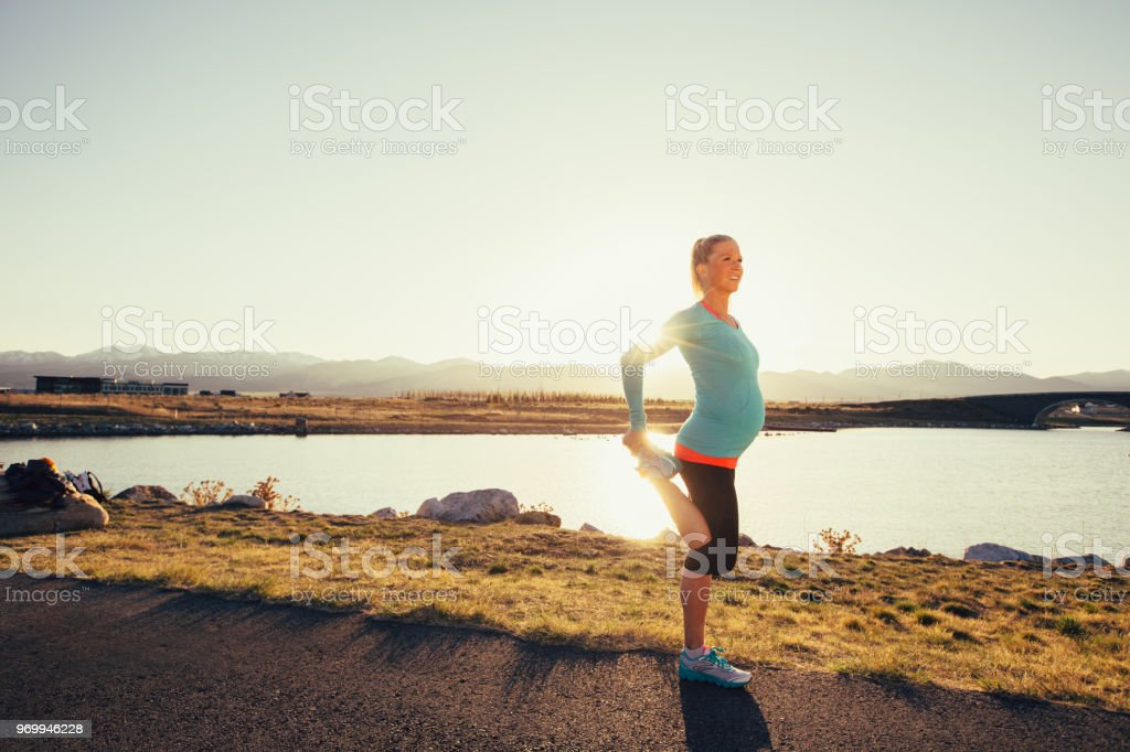 Pregnant Female Runner Stretches on a Trail at Sunset stock photo
