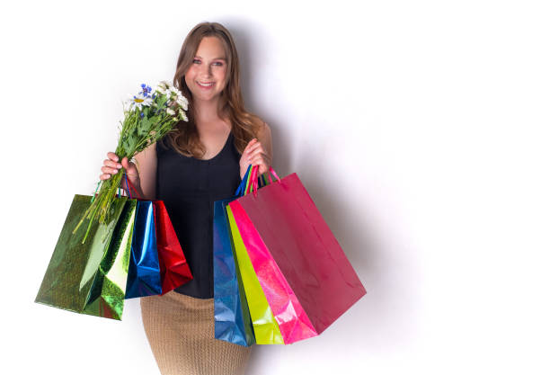 pregnant girl with flowers and bags stock photo