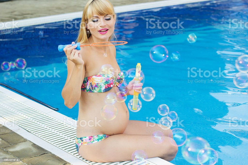Pregnant happy girl is making soap bubbles near swimming pool stock photo