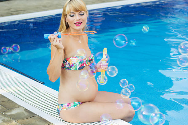 pregnant happy girl is making soap bubbles near swimming pool - makeup for pregnant women stock photos and pictures