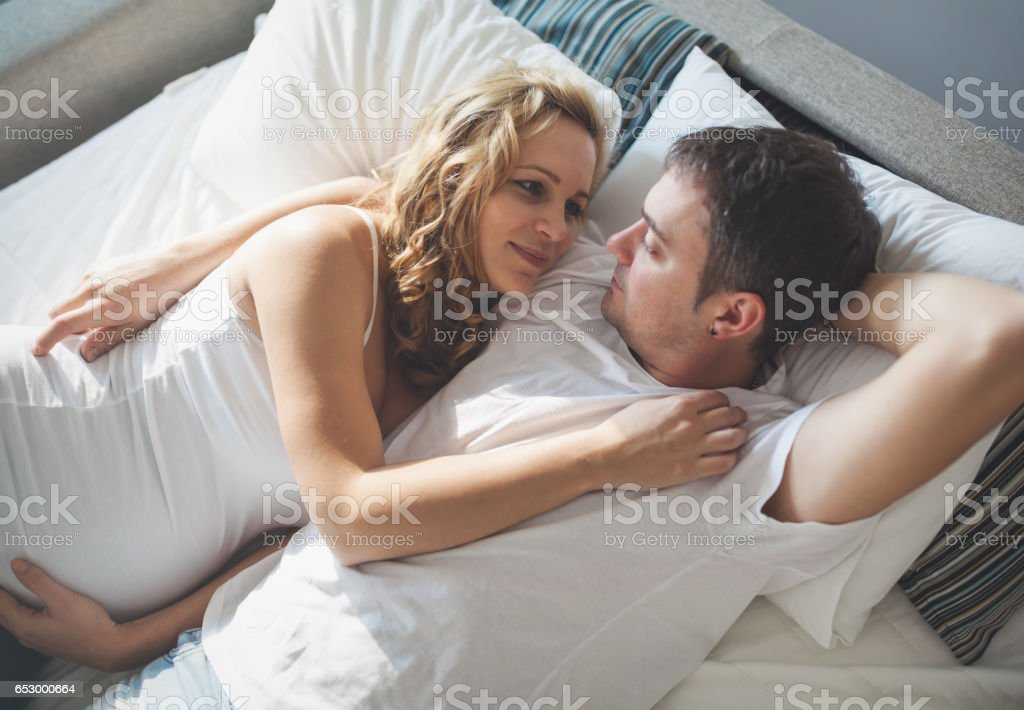 Pregnant happy wife lying in bed with husband stock photo