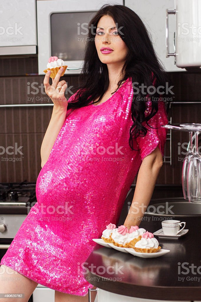 Pregnant happy woman in kitchen eating cakes stock photo