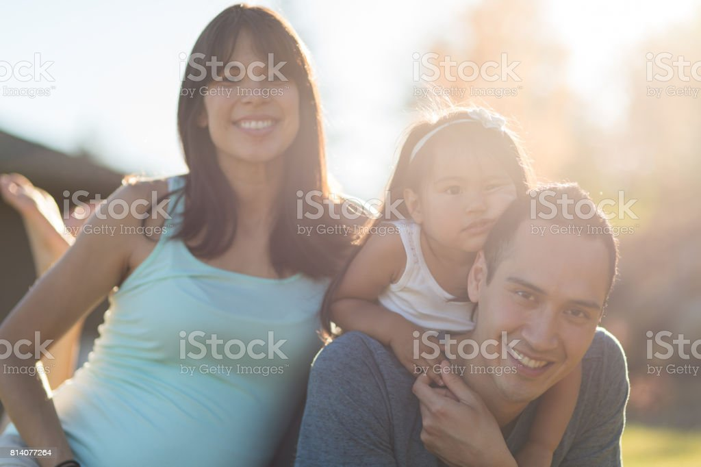 Pregnant Hawaiian Couple and Young Daughter in Park Outdoors stock photo