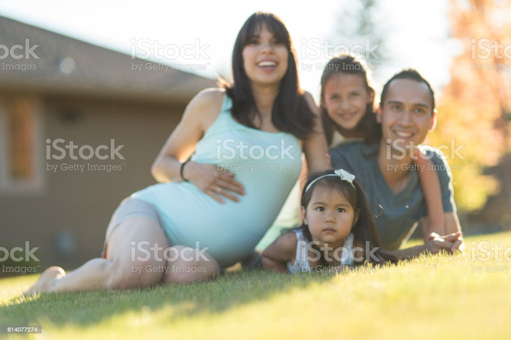 Pregnant Hawaiian Couple and Young Daughters in Park Outdoors stock photo