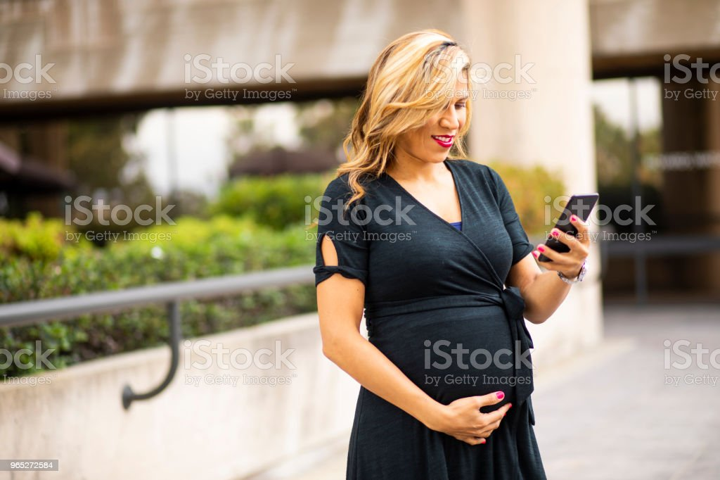 Pregnant Hispanic Businesswoman Texting on Smartphone zbiór zdjęć royalty-free