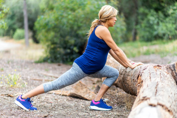 Pregnant Hispanic Woman Stretching A beautiful pregnant hispanic woman stretches during a workout hamstring stock pictures, royalty-free photos & images