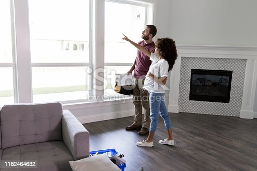 Serious pregnant homeowner points at something through the window in her living room while talking with a building contractor or repairman.