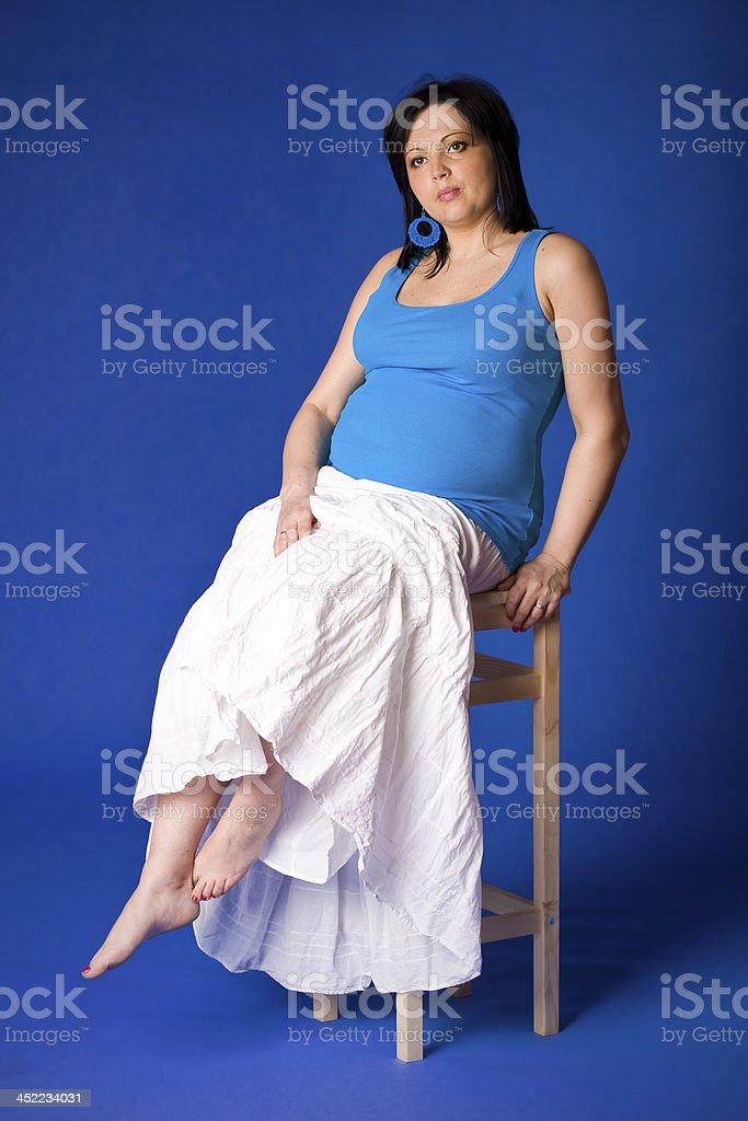 Pregnant lady portrait in blue stock photo