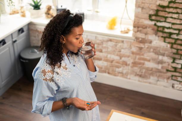 Schwangere Dame nimmt ihre Vitamine mit Wasser. – Foto