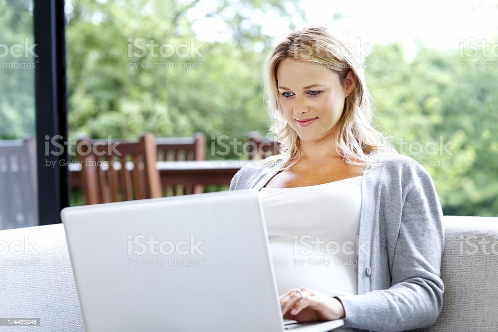 Pregnant lady working on laptop - Indoor royalty-free stock photo