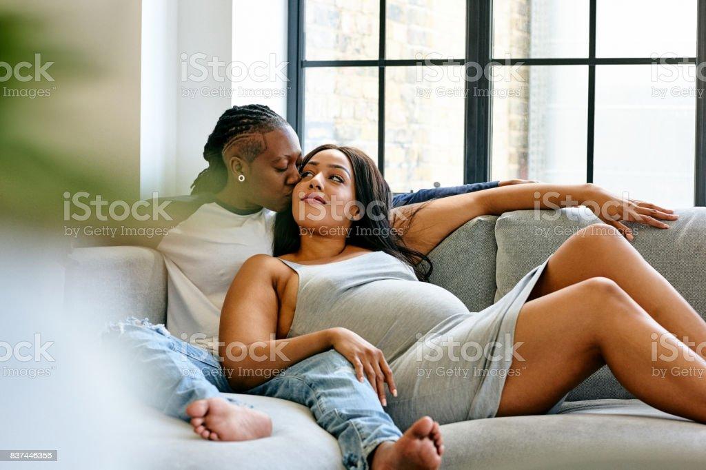 Pareja de lesbianas embarazada relajante en el sofá - foto de stock