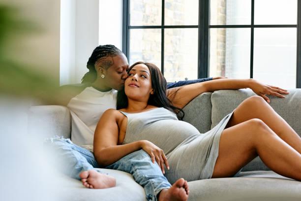 zwangere lesbisch koppel ontspannen op de sofa - lesbische stockfoto's en -beelden