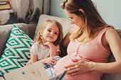 young pregnant loving mother reading book to toddler daughter at home, casual lifestyle in real life interior