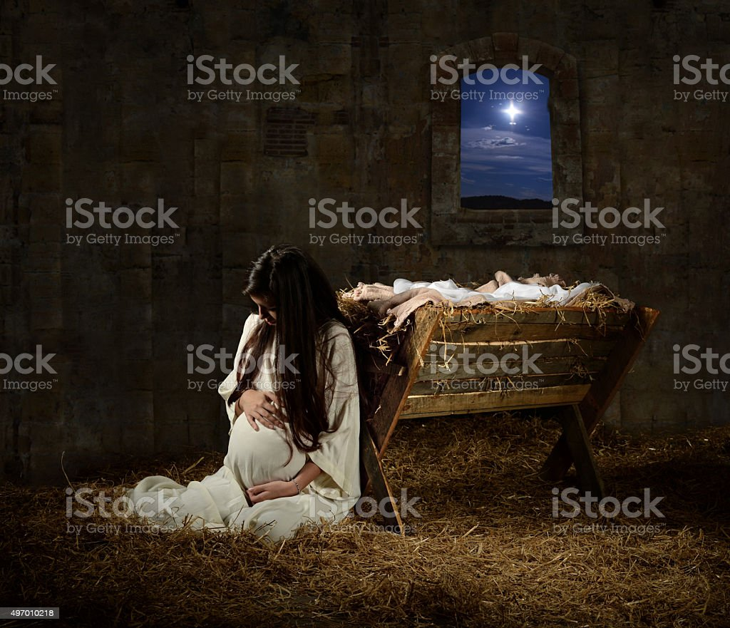 Pregnant Mary Leaning on Manger Young pregnant Mary praying leaning on manger on Christmas Eve 2015 Stock Photo