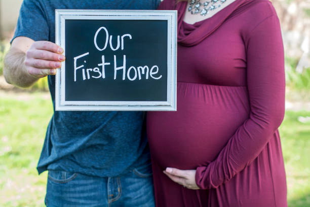 pregnant mom and dad holding sign for our first home as new homeowners stock photo