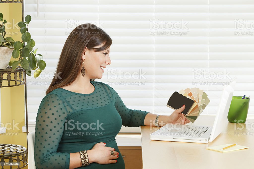 Pregnant mom working on a laptop looking at color samples. royalty-free stock photo