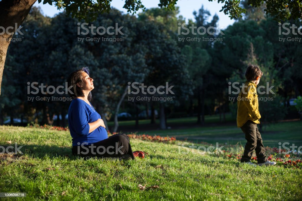 Pregnant Mother And 5 Years Old Son In Public Park Stock