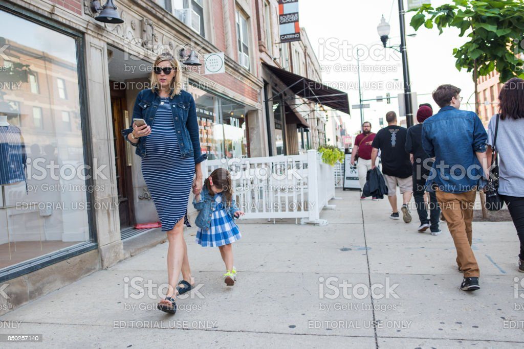 Pregnant mother and child skipping along the street in Chicago stock photo