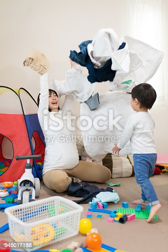 954356678istockphoto Pregnant mother and child throwing laundry together in living room 945017188