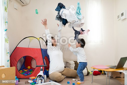 954356678istockphoto Pregnant mother and child throwing laundry together in living room 945017228
