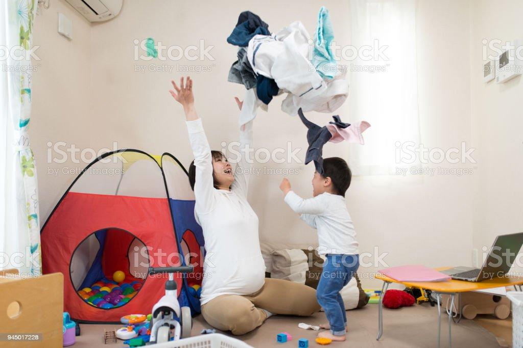 妊娠中の母親と居間で一緒にランドリーを投げる子 ストックフォト