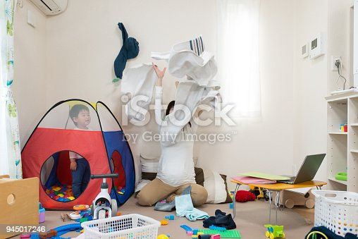 954356678istockphoto Pregnant mother and child throwing laundry together in living room 945017246