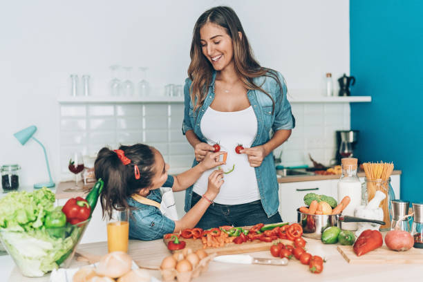 Pregnant mother and daughter making vegetable smiley face stock photo