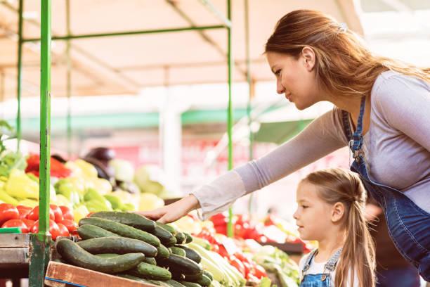 schwangere mutter und ihre tochter kaufen gemüse - latzhose für schwangere stock-fotos und bilder