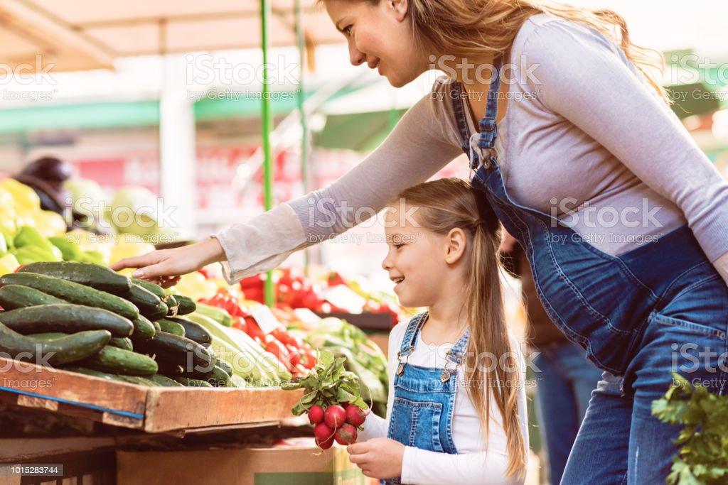 Schwangere Mutter und ihre Tochter kaufen Gemüse – Foto
