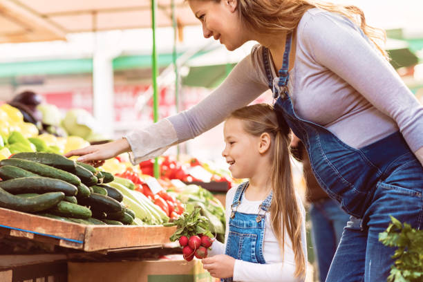 pregnant mother and her daughter buying vegetables - mercato frutta donna foto e immagini stock
