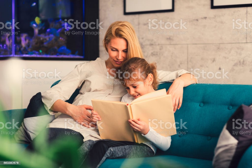 Pregnant Mother and her daughter reading book stock photo