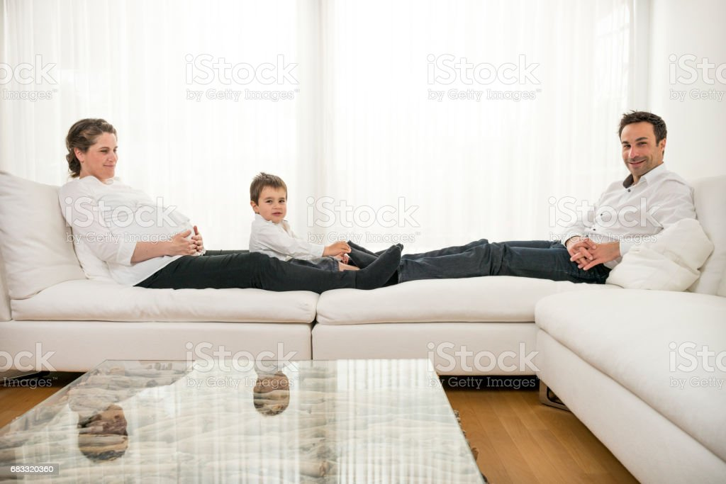 Pregnant mother and her family sitting on the sofa royalty-free stock photo