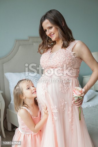 Pregnant mother and little daughter. Happy mother's day concept