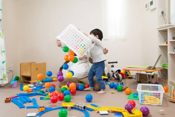pregnant mother and toddler playing together with toy in untidy room - toy stock pictures, royalty-free photos & images