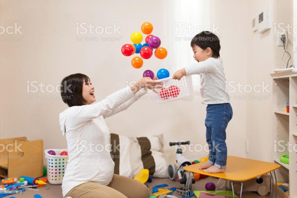 妊娠中の母親と幼児のおもちゃで一緒に遊ぶ ストックフォト