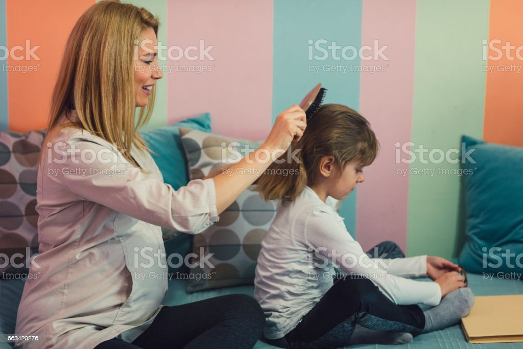 Pregnant Mother Brushing Daughters Hair stock photo