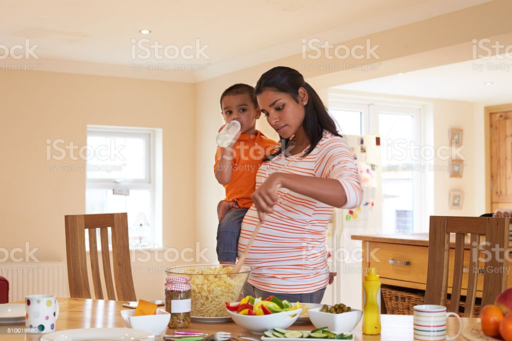 Pregnant Mother Carrying Son Whilst Making Salad In Kitchen stock photo