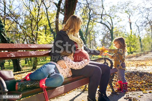 istock Pregnant mother enjoying with her two daughters in park on sunny autumn day. 922368488