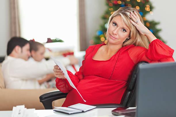 madre incinta con sua famiglia frustrato di natale fatture - holiday and invoice family foto e immagini stock