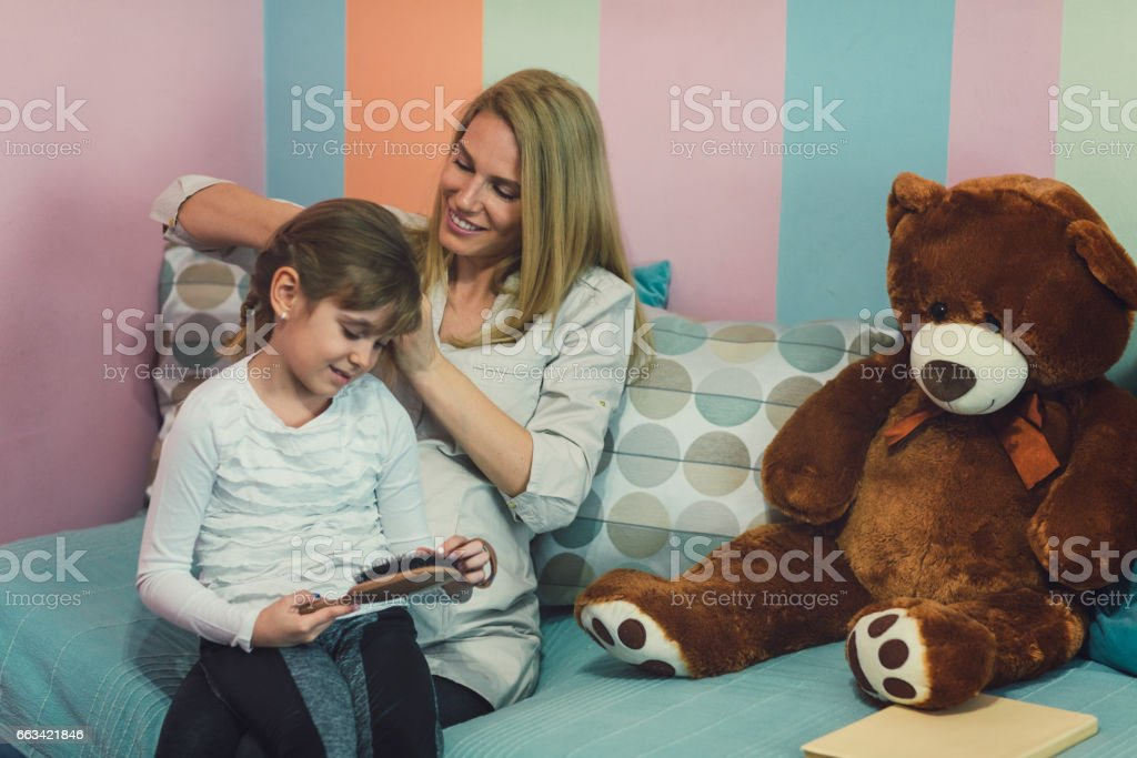 Pregnant Mother making Braid to Daughter stock photo