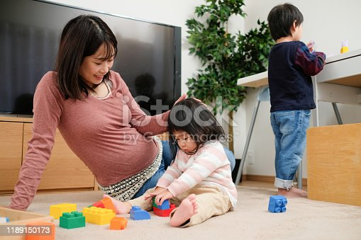 1053936526 istock photo Pregnant mother playing in room with baby and child 1189150173