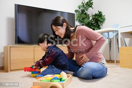 1053936526 istock photo Pregnant mother playing in room with child 1189150183