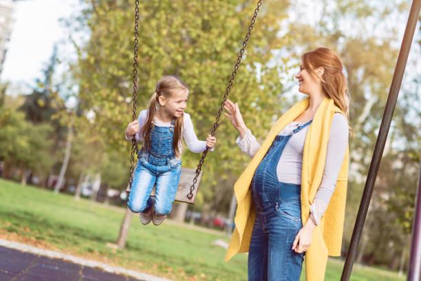 schwangere mutter schob ihre tochter glücklich auf der schaukel im park - latzhose für schwangere stock-fotos und bilder